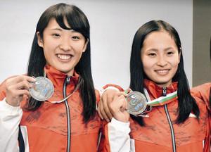 世界選手権から帰国し、メダルを手に笑顔を見せる森(左、右は岸彩乃)