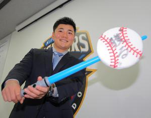 来季の目標「獲る」と書いたボールをライトセーバーで打つ日本ハム・清宮