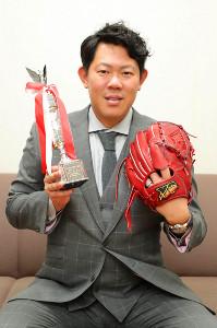 3冠達成の記念トロフィーと新作のグラブを持ち、撮影に応じる山口俊(カメラ・義村 治子)