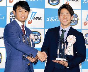 受賞し握手をする高山俊(左)と鈴木大地
