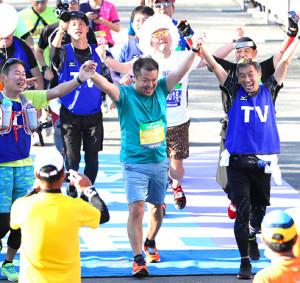ブラックマヨネーズ・小杉(中央)はスタッフと手をつなぎ、笑顔でゴール