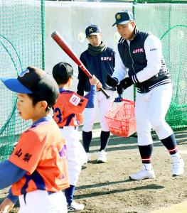 小学生に打撃を指導する山梨学院・野村(右)