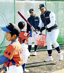 小学生に打撃を教える山梨学院・野村(右)