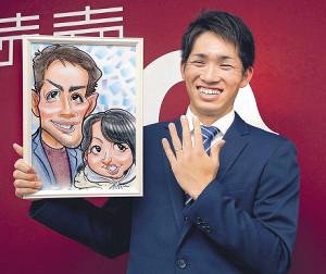 年俸アップでサインした高橋は、2歳年上の一般女性との結婚を発表し、似顔絵を手に笑顔を見せた(カメラ・泉 貫太)