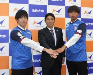 富山のユニホームを着て記念撮影に応じる法大サッカー部の末木裕也(左)と松沢彰(右)。中央は富山の黒部光昭強化部長