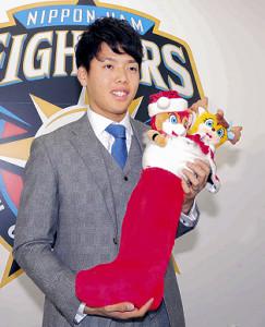 マスコットが入ったクリスマスの靴下を持つ杉浦