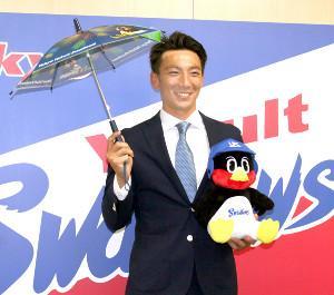 ヤクルトと正式契約を結び、応援傘を手に笑顔の嶋