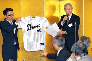 メモリアルゲームで、オリックスの選手たちが着用するユニホームを発表する山田久志OB会長(右)