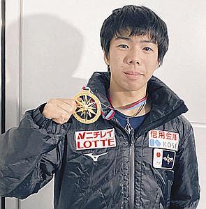 メダルを掲げる佐藤駿