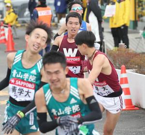 早大2区・太田智樹(左から3人目)は3区・井川龍人にタスキを渡す