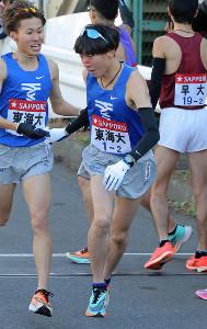 タスキを受けた東海大の2区、塩沢稀夕(右)(カメラ・泉 貫太)