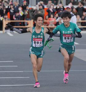 1位通過の青学大4区・吉田祐也(左)から、青学大5区・飯田貴之にタスキが渡る
