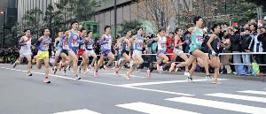 大勢の観客が見つめる中、大手町を一斉にスタートする1区の選手たち(カメラ・相川 和寛)