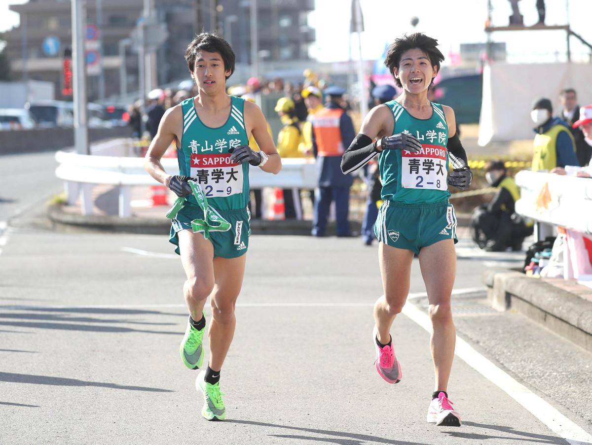 青学大8区・岩見秀哉(右)から青学大9区・神林勇太にトップでタスキが渡る