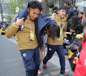 総合10位でゴールした東洋大10区・及川瑠音(中)を抱える相沢晃(左)と今西駿介