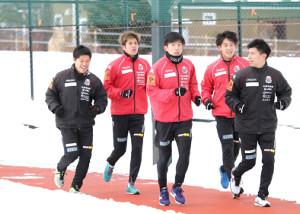 雪の積もる中をランニングする札幌の(左から)竹内コーチ、DF進藤、MF金子、MF高嶺、大塚フィジカルコーチ