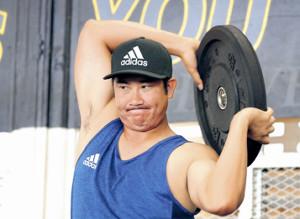 トレーニングでバーベルプレートを持ち上げ、肉体を鍛える菅野(カメラ・中島 傑)