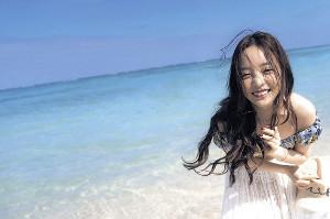 沖縄の美しい海をバックに無邪気な笑顔を見せるハラさん
