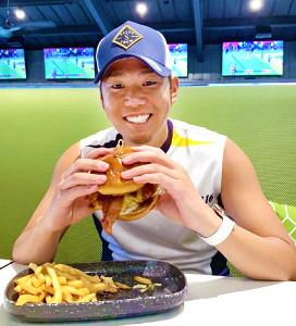 練習の合間、本場のハンバーガーを頬張った西勇は笑顔を見せた(カメラ・中村 晃大)