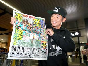 自主トレ先のグアムから帰国した横浜C・三浦。母校・静岡学園の優勝を報じる本紙一面をうれしそうに見つめた(カメラ・竜田 卓)