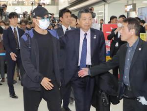 桃田賢斗(左)が帰国し、関係者の出迎えを受ける