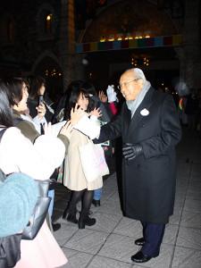 ミッキーマウスのミットを付けて準社員たちとタッチするオリエンタルランド加賀見俊夫会長