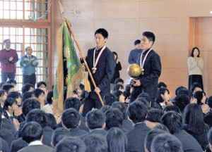 優勝旗を持ち報告会に入場する静岡学園サッカー部の阿部主将(左)