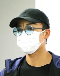 帰国した桃田の額には、サングラスとマスクで隠せない大きな裂傷の痕があった(カメラ・竜田 卓)