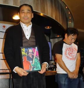 ケンドー・ナガサキさんの遺影を手に黙とうを捧げる谷津嘉章(左)
