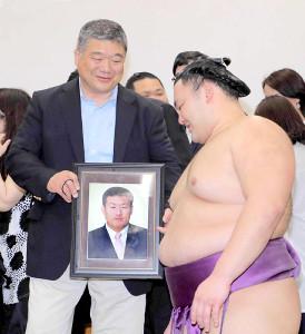 昨年の5月、優勝した朝乃山(右)を恩師の浦山監督の遺影を手に祝福した近大相撲部の伊東監督