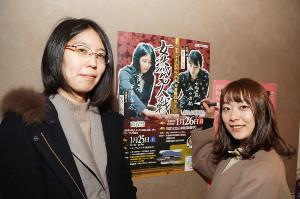 ポスターにサインをする里見香奈女流名人(左)と谷口由紀女流三段