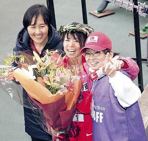 花束を手に笑顔の松田(中)(左はダイハツ・山中監督、右は母・明美さん)
