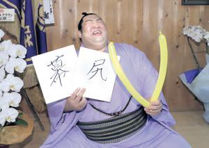 「幕尻」と記した色紙と「V」バルーンを持ち、爆笑しながらポーズをとる徳勝龍(カメラ・関口 俊明)