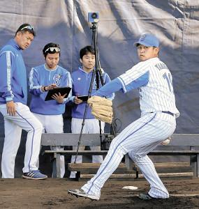 ブルペンに導入されたハイスピードカメラを背に投球練習する山崎(カメラ・岸 慎也)