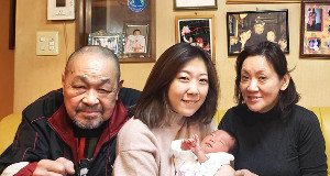 誕生した夢実さんを抱く映理さん(中)とザ・グレート・カブキ夫妻(米良明久さん、安子さん)