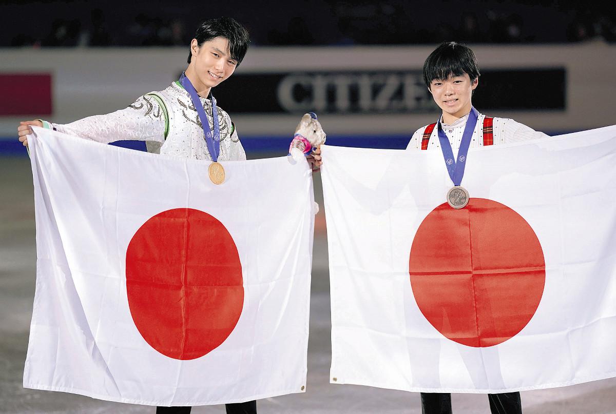 表彰式で日の丸を手に笑顔を見せる羽生(左)と、国際大会デビュー戦で3位となった鍵山(カメラ・矢口 亨)