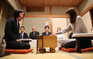 初手をさす谷口由紀女流三段(左は後手・里見香奈女流名人)(カメラ・谷口 健二)