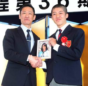 小林脩斗君は母・優子さんの遺影を手に、父・久晃さんと握手をかわした