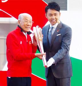 北島さん(右)から聖火リレーのトーチを受け取る矢崎さん