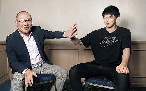 互いの手の大きさを比べる高木豊氏(左)と佐々木朗