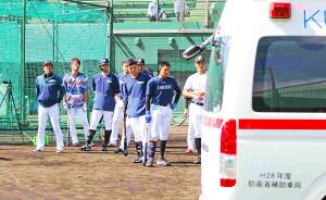 12日、城石コーチが乗った救急車を見送る日本ハム関係者(かいぎんスタジアム国頭で)