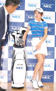 フォトセッション前に、NECロゴの位置を確認する安田祐香(右)