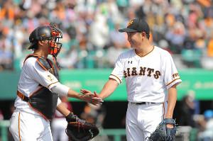 3回を投げ終え小林誠司(左)とハイタッチをする菅野智之