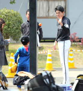 ブルペンで投球を終えた練習中、子供とキャッチボールをする佐々木朗