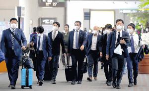 沖縄キャンプを打ち上げた原監督(中央)は感染防止のためマスクを着用。那覇空港で取材を受けながら搭乗ゲートに向かう(カメラ・中島 傑)