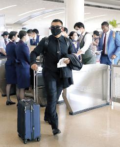 黒いマスクに黒ずくめの姿で帰京するパーラ