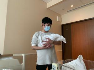 誕生した第3子をだっこする石田