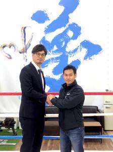プロ復帰を表明し、元世界王者の石田会長(左)と握手する高山勝成