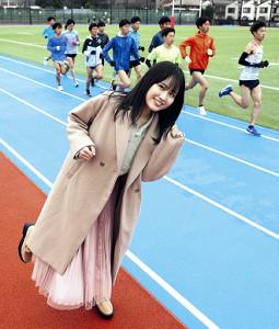 練習する麗沢大の選手たちをまねて笑顔でポーズをとる西村菜那子