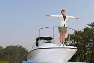 昨年の大会で優勝し、副賞のボートの上でポーズをとる成田美寿々